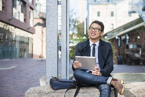 Young businessman sitting outside holding tablet